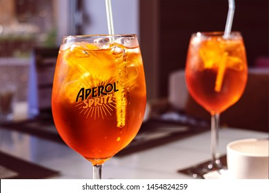 Moscow, Russia - July 2019: Refreshing Delicious Alcoholic Cocktail Aperol Spitz With Ice In Glass Covered Drops Or Splashes Of Water. Pleasant Evening In Respectable Restaurant With Aperol Spritz.