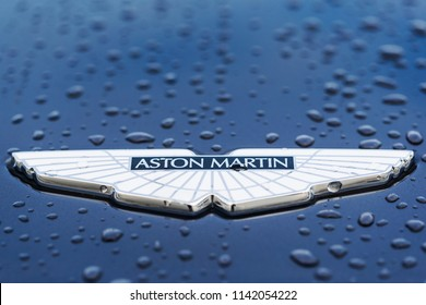 Moscow, Russia - July 22, 2018:  A close-up of the Aston Martin logo on a blue car with drops of water. Aston Martin is a British manufacturer of luxury sports cars founded in 1913.