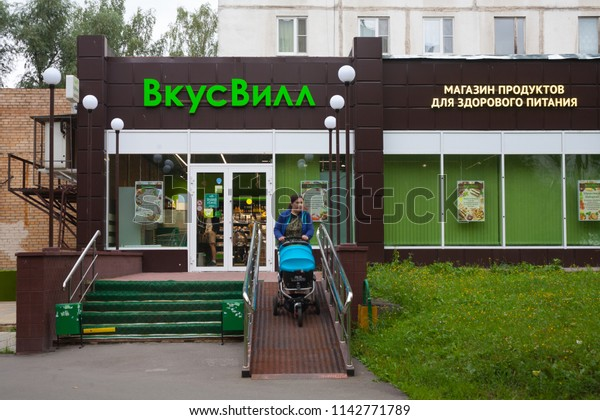 MOSCOW, RUSSIA - JULY 24, 2018: Vkusvill food store building and woman with baby stroller in Muranovskaya street. This street is located in Bibirevo district of Moscow.