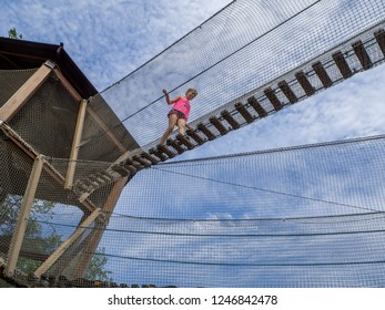 MOSCOW, RUSSIA - JULY 26, 2018: Unidentified girl goes on extreme rope ladder  way with safety net in children's amusement park Lukomorye in Moscow, Russia on July 26, 2018.