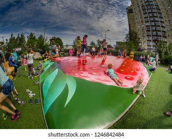 MOSCOW, RUSSIA - JULY 26, 2018: Unidentified joyful children are jumping fun on inflatable trampoline in form of strawberry in children's amusement park Lukomorye in Moscow, Russia on July 26, 2018.