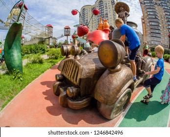 MOSCOW, RUSSIA - JULY 26, 2018: Unidentified boys play with car playground equipment in children's amusement park Lukomorye in Moscow, Russia on July 26, 2018.