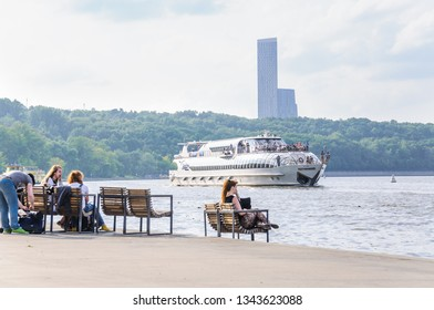 """MOSCOW, RUSSIA - July 27, 2016: Super-yacht """"Butterfly"""" of the flotilla of the hotel """"Radisson Royal"""" on the Moscow river. Young people resting on the benches on the waterfront"""