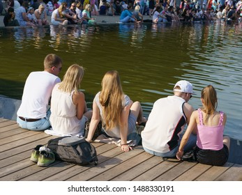 Moscow, Russia - July 27, 2019: People resting near fountain in the Gorky Park in hot summer day. Crowd of people near water. International Hamburger Day. People like the freshness of fountain water.