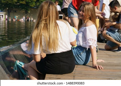 Moscow, Russia - July 27, 2019: People resting near fountain in the Gorky Park in hot summer day. Crowd of people near water. International Hamburger Day. People freshen up near fountain.