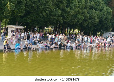 Moscow, Russia - July 27, 2019: People resting near fountain in Gorky Park in hot summer day. Crowd of people near water. International Hamburger Day. People freshen up near fountain. Natural light.