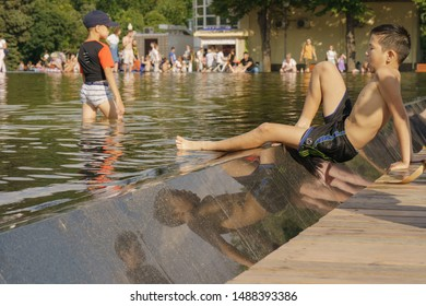 Moscow, Russia - July 27, 2019: People resting near fountain in Gorky Park in hot summer day. Crowd of people near water. International Hamburger Day. People freshen up near fountain, boys wet legs