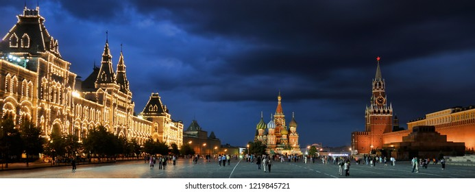 Moscow, Russia - July 28, 2009 Panorama of Red Square with illuminated St. Basil's Cathedral, GUM mall, Spasskaya Kremlin Tower, and Lenin's Tomb under umpressive twilight skies in summer evening.