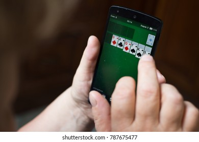 Moscow, RUSSIA - July 29th, 2017: Old woman playing the Solitaire game at the smartphone