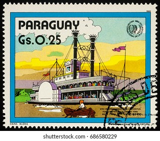 """Moscow, Russia - July 30, 2017: A stamp printed in Paraguay shows old Mississippi steamboat - a scene from Adventures of Tom Sawyer by Mark Twain, series """"International Year of Youth"""", circa 1985"""