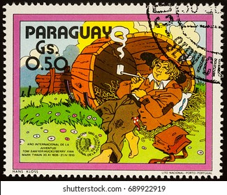 """Moscow, Russia - July 30, 2017: A stamp printed in Paraguay shows Huckleberry Finn in the old barrel, Adventures of Tom Sawyer by Mark Twain, series """"International Year of Youth"""", circa 1985"""