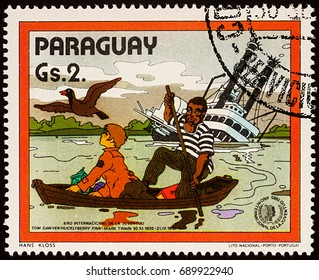 """Moscow, Russia - July 30, 2017: A stamp printed in Paraguay shows Finn and Joe in boat near Sinking Riverboat, Adventures of Tom Sawyer by Mark Twain, series """"International Year of Youth"""", circa 1985"""