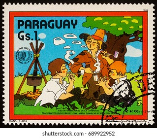 """Moscow, Russia - July 30, 2017: A stamp printed in Paraguay shows Huckleberry Finn and Friends by Campsfire, Adventures of Tom Sawyer by Mark Twain, series """"International Year of Youth"""", circa 1985"""