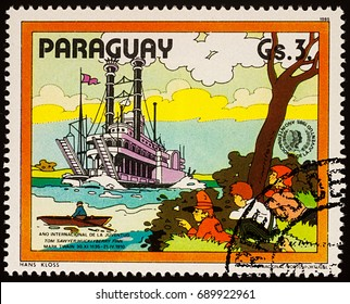 """Moscow, Russia - July 30, 2017: A stamp printed in Paraguay shows Finn, Friends and Riverboat on Mississippi, Adventures of Tom Sawyer by Mark Twain, series """"International Year of Youth"""", circa 1985"""