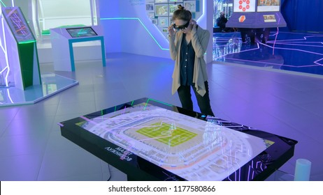 MOSCOW, RUSSIA - July 30, 2018: Smart City Exhibition. Augmented reality experience: woman using special glasses and looking at display table with interactive 3d virtual maquette of stadium Luzhniki