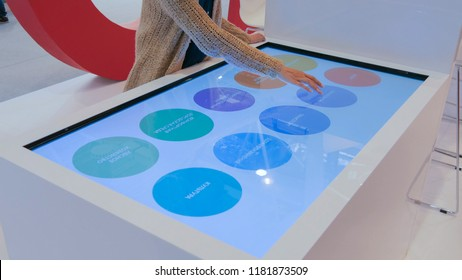 MOSCOW, RUSSIA - July 30, 2018: Moscow Urban Forum. Woman using interactive touchscreen display table at urban exhibition - scrolling and touching