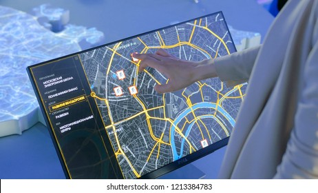 MOSCOW, RUSSIA - July 30, 2018: Smart City Exhibition. Woman using interactive touchscreen display with virtual map of Moscow at modern technology show