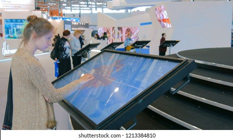 MOSCOW, RUSSIA - July 30, 2018: Moscow Urban Forum. Woman using interactive touchscreen display at urban exhibition - scrolling and touching. Education and technology concept