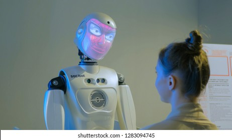 MOSCOW, RUSSIA - July 30, 2018: Robostation - future exhibition. Funny humanoid robot with display spider man face talking with woman and changing faces at technology exhibition