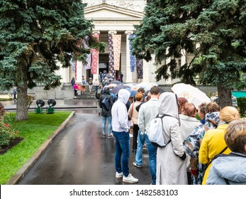 MOSCOW, RUSSIA - JULY 31, 2019: queue of visitors to gate of Pushkin State Museum of Fine Arts on rainy day in Moscow city. Pushkin Museum is the museum of European art, located in Volkhonka street