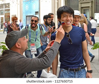 MOSCOW, RUSSIA - JULY 5, 2018: 2018 FIFA World Cup. Street artist draws Russian flag to happy fans on Nikolskaya street in center of Moscow