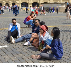 MOSCOW, RUSSIA - JULY 5, 2018: 2018 FIFA World Cup. Tired fans are sitting on cobbles of Red Square
