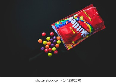 MOSCOW, RUSSIA - JULY 5, 2019: Colorful skittles candies on a black background.
