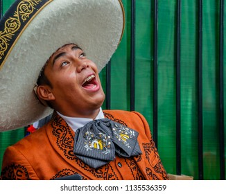 Moscow, Russia - July 7, 2018: Mexican street musician mariachi in traditional clothes and sombrero sings a serenade, close-up portrait