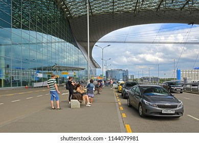 MOSCOW, RUSSIA - JULY 7, 2018: Sheremetyevo International Airport, Terminal D. Passengers and travelers with suitcases are waiting for bus and taxi