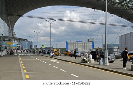 MOSCOW, RUSSIA - JULY 7, 2018: Sheremetyevo International Airport, Terminal D. Passengers and travelers with suitcases on background of hotels