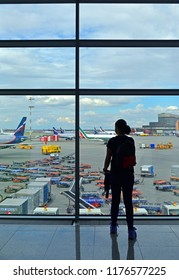 MOSCOW, RUSSIA - JULY 7, 2018: Sheremetyevo International Airport, Terminal D. Silhouette of passenger in airport lounge waiting for flight aircraft