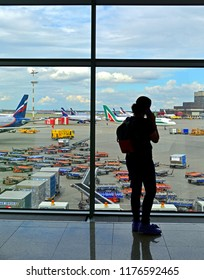 MOSCOW, RUSSIA - JULY 7, 2018: Sheremetyevo International Airport, Terminal D. Silhouette of passenger with phone in airport lounge waiting for flight aircraft