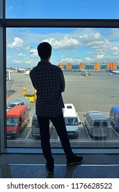 MOSCOW, RUSSIA - JULY 7, 2018: Sheremetyevo International Airport, Terminal D. Silhouette of man in airport lounge waiting for flight aircraft