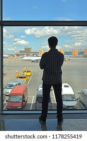 MOSCOW, RUSSIA - JULY 7, 2018: Sheremetyevo International Airport, Terminal D. Silhouette of young man with glasses in airport lounge waiting for flight aircraft
