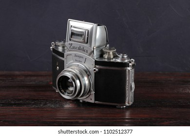 MOSCOW, RUSSIA, JUNE 01, 2018. The old German 35 mm SLR camera Kine Exakta with Carl Zeiss lens Tessar 2,8/50, released 1938, on a wooden background.