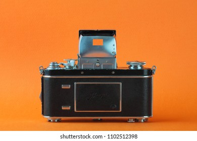 MOSCOW, RUSSIA, JUNE 01, 2018. The old German 35 mm SLR camera Kine Exakta with Carl Zeiss lens Tessar 2,8/50, released 1938, on a orange background.