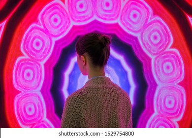 MOSCOW, RUSSIA - JUNE 01, 2019: Woman standing in front of large interactive display with colorful abstact video at modern immersive exhibition. Education, digital art and entertainment concept