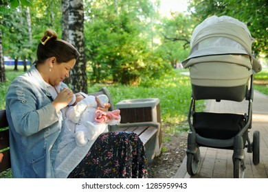 MOSCOW, RUSSIA - June 02, 2018 Milk Break – The Time to Feed. Mother feeding a baby from a bottle with breast milk on a bench in the park Berezovaya Roshcha (Birch Grove), metro station Polezhaevskaya