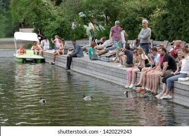Moscow, Russia, June 02, 2019: people sit on a wooden embankment, legs dangling down by the water. Gorky Park, Golitsyn ponds