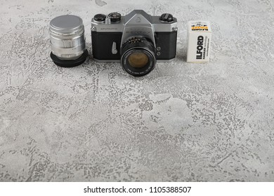 MOSCOW, RUSSIA, JUNE 05, 2018. The old Japan 35 mm SLR camera Asahi Pentax Spotmatik with 55 mm Pentax lens, released 1971 with film packings lford & Kodak on black cement background .