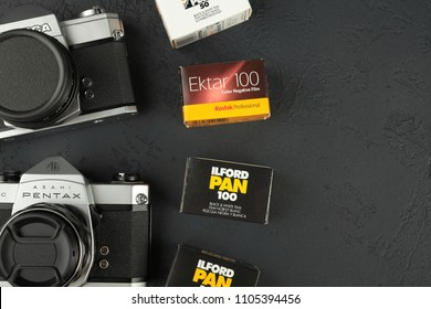 MOSCOW, RUSSIA, JUNE 05, 2018. The old Japan 35 mm cameras Pentax Spotmatik, Fujica ST-701, Yashica J-3 with 50 mm lenses, released 70's, with film packings lford & Kodak on black cement background.