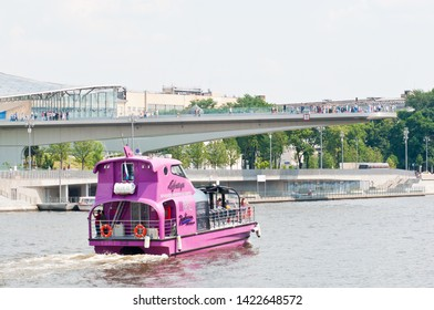 """MOSCOW, RUSSIA - JUNE 09, 2019:   Radisson Royal Flotilla yacht on Moskva-river and  """"floating bridge"""" of the park """"Zaryadye"""" in summer day"""