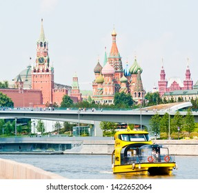 MOSCOW, RUSSIA - JUNE 09, 2019:   Spasskaya Tower and Cathedral of Vasily the Blessed (Saint Basil's Cathedral) on Red Square and Radisson Royal Flotilla yacht on Moskva-river in sunny summer day