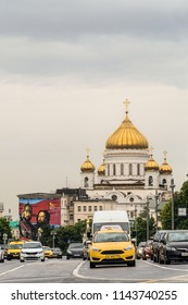 Moscow, Russia - June 10, 2018: Roadway with cars on Mokhovaya Street in the center of Moscow. View of the Cathedral of Christ the Savior. City Yandex taxi in the foreground.