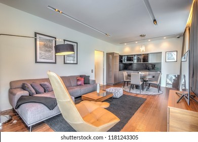 MOSCOW, RUSSIA - JUNE 10, 2018: Modern living room with sofas and leather armchair, pillows in including creative wooden table with ornaments items. Long cupboard or TV stand near panoramic windows
