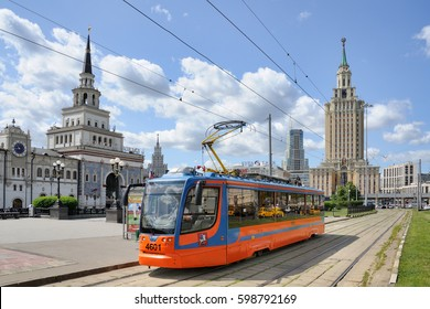 MOSCOW, RUSSIA - June 12, 2015 (Day of Russia) The low-floor tramcar KTM-23 on a tram stop at Komsomolskaya square in a background of Kazansky Railway station and Hilton Lenigradskaya hotel.