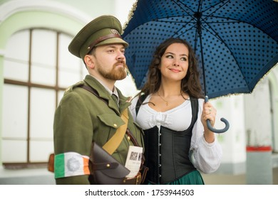 Moscow Russia June 12, 2017 historical festival times and epochs. Historical interpreter, re-enactors In uniform. World War I soldier with a beautiful young woman in a vintage dress with an umbrella.