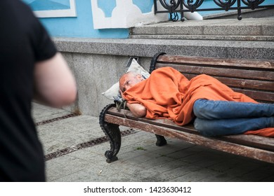 Moscow, RUSSIA - June 12, 2019: homeless man lying on a bench covered with an orange rug. A crowd passes by