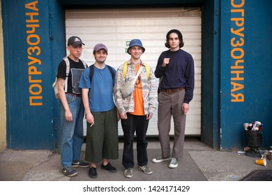 Moscow, RUSSIA - June 12, 2019: Four fashionably dressed young people stand against a white corrugated gate.