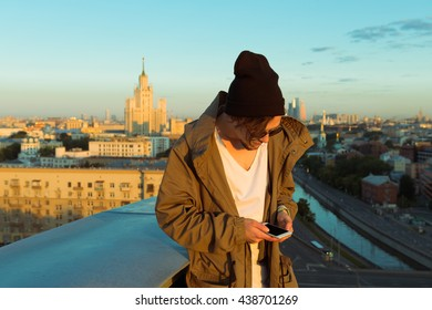 MOSCOW, RUSSIA - JUNE 13, 2016: Young and brave male sitting on the edge of high roof looking at phone similar to iphone and stunning view of the city in summer during dawn